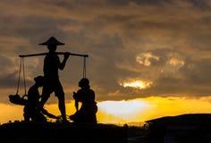 Siluetta dell'agricoltore tailandese tradizionale Carry The Baskets di riso in sua mano con le donne sul pavimento all'angolo Fes Immagini Stock