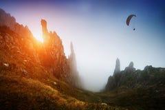 Siluetta dell'aliante sopra la valle della montagna nebbiosa Fotografia Stock