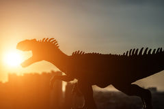 Siluetta dell'allosauro e delle costruzioni in un tempo di tramonto Immagine Stock Libera da Diritti