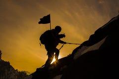 Siluetta dell'alpinista e del tramonto Fotografie Stock