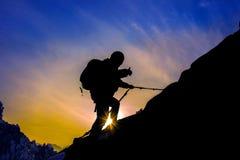 Siluetta dell'alpinista e del tramonto Fotografia Stock