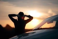 Siluetta dell'autista femminile felice accanto alla sua automobile fotografia stock libera da diritti