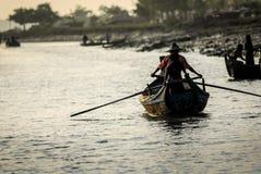 Siluetta dell'imbarcazione a remi quotidiana di vita di mattina Fotografia Stock