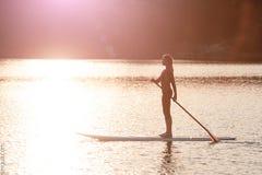 Siluetta dell'imbarco della pagaia della ragazza a sunset01 immagini stock libere da diritti