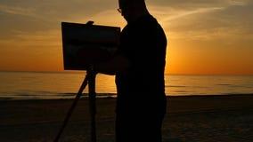 Siluetta dell'immagine della pittura dell'artista sul movimento lento del fondo del cielo stock footage