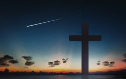 Siluetta dell'incrocio della croce a tempo di tramonto e del cielo notturno con il fondo della stella cadente immagini stock