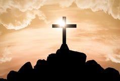 Siluetta dell'incrocio di Gesù sopra il tramonto fotografie stock libere da diritti