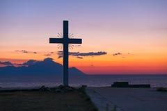 Siluetta dell'incrocio e del monte Athos ad alba o al tramonto con panorama del mare Immagine Stock