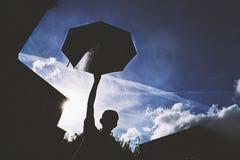 Siluetta dell'ombrello in Sun nuvoloso fotografia stock libera da diritti