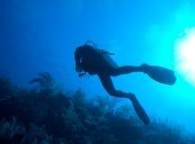 Siluetta dell'operatore subacqueo con il disco del sole dietro immagini stock