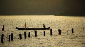 Siluetta dell'uomo anziano da solo in barca fotografia stock libera da diritti
