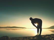 Siluetta dell'uomo attivo che si esercita e che allunga sulla spiaggia del lago all'alba Fotografia Stock