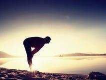 Siluetta dell'uomo attivo che si esercita e che allunga sulla spiaggia del lago all'alba Fotografie Stock