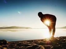 Siluetta dell'uomo attivo che si esercita e che allunga sulla spiaggia del lago all'alba Immagini Stock