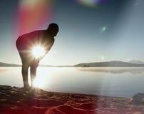 Siluetta dell'uomo attivo che si esercita e che allunga sulla spiaggia del lago all'alba Fotografia Stock Libera da Diritti