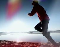 Siluetta dell'uomo attivo che si esercita e che allunga sulla spiaggia del lago all'alba Immagine Stock Libera da Diritti