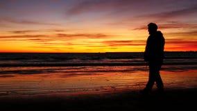 Siluetta dell'uomo che cammina sulla spiaggia con il tramonto (4K) archivi video