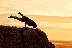 Siluetta dell'uomo che fa meditazione di yoga contro il bello cielo con le nuvole Immagini Stock Libere da Diritti
