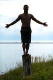 Siluetta dell'uomo che fa yoga su un ceppo in natura Fotografie Stock Libere da Diritti