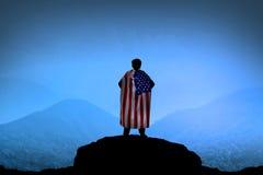 Siluetta dell'uomo che indossa la bandiera di U.S.A. come capo sulla montagna Fotografie Stock Libere da Diritti