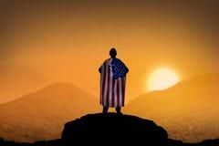 Siluetta dell'uomo che indossa la bandiera di U.S.A. come capo sulla montagna Immagini Stock
