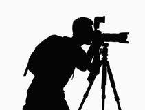 Siluetta dell'uomo che prende le immagini con la macchina fotografica sul treppiede. Fotografia Stock