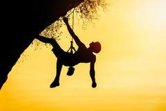 Siluetta dell'uomo che scala al tramonto Lo scalatore durante il ro Immagine Stock