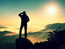 Siluetta dell'uomo che scala su sulla scogliera La viandante scalata fino al picco gode della vista Immagine Stock