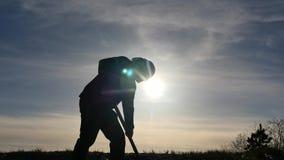 Siluetta dell'uomo che scava con la vanga - sfarfallamento luminoso del sole video d archivio