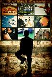Siluetta dell'uomo che si siede davanti alla video parete Immagini Stock