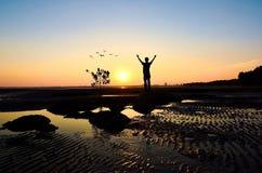Siluetta dell'uomo che solleva le sue mani o a braccia aperte Fotografia Stock