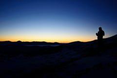 Siluetta dell'uomo che sta sulla cima della montagna per godere del cielo colourful Fotografie Stock
