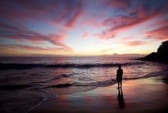 Siluetta dell'uomo che sta sulla spiaggia al tramonto Immagine Stock