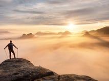 Siluetta dell'uomo con i pali a disposizione L'alba della molla e la guida soleggiate del turista restano sulla scogliera taglien Fotografia Stock Libera da Diritti