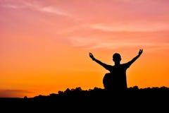 Siluetta dell'uomo con la mano aperta dello zaino sulla parte posteriore di tramonto del cielo Immagini Stock Libere da Diritti