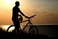 Siluetta dell'uomo con una bicicletta Immagine Stock