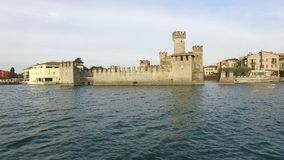 Siluetta dell'uomo Cowering di affari Il castello di Scaliger in Sirmione Lago Garda, Italia 4K video d archivio