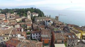 Siluetta dell'uomo Cowering di affari Il castello di Scaliger in Sirmione Lago Garda, Italia 4K archivi video