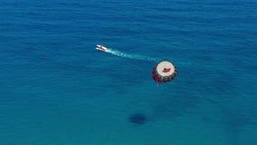 Siluetta dell'uomo Cowering di affari La gente che vola su un paracadute variopinto rimorchiato in imbarcazione a motore parasail stock footage