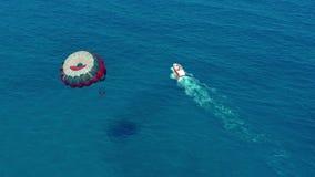 Siluetta dell'uomo Cowering di affari La gente che vola su un paracadute variopinto rimorchiato in imbarcazione a motore parasail archivi video