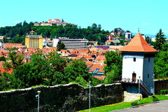 Siluetta dell'uomo Cowering di affari Paesaggio urbano tipico della città Brasov Fortezza medioevale Immagini Stock