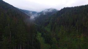 Siluetta dell'uomo Cowering di affari Sorvolare le alte montagne in belle nuvole Colpo della camera aerea Ventili le nubi nebbia  video d archivio
