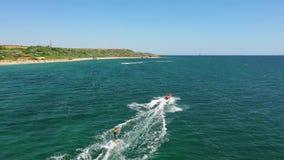 Siluetta dell'uomo Cowering di affari Sorvolare wakeboarder che pratica il surfing dietro la barca sul mare Imbarco di risveglio  archivi video