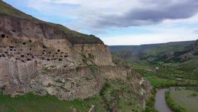 Siluetta dell'uomo Cowering di affari Vardzia ? un sito del monastero della caverna nella Georgia del sud stock footage