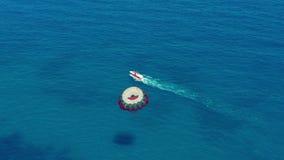 Siluetta dell'uomo Cowering di affari Volando con il paracadute dietro una barca Sport acquatico estremo nel mare Parasailing stock footage