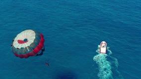 Siluetta dell'uomo Cowering di affari Volando con il paracadute dietro una barca Sport acquatico estremo nel mare Parasailing video d archivio