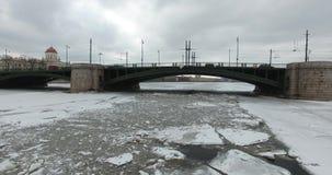 Siluetta dell'uomo Cowering di affari Volo lungo il fiume Neva in freddo nuvoloso di inverno Ponte sopra il fiume Pietroburgo L'a stock footage