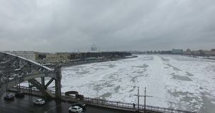 Siluetta dell'uomo Cowering di affari Volo lungo il fiume Neva in freddo nuvoloso di inverno Ponte sopra il fiume Pietroburgo L'a archivi video
