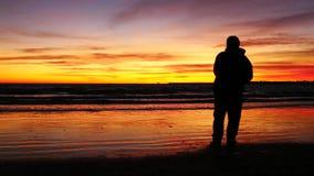 Siluetta dell'uomo davanti al tramonto sulla spiaggia (4K) stock footage