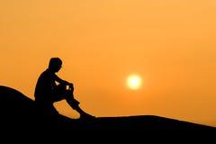 Siluetta dell'uomo di seduta su roccia al tramonto Immagini Stock